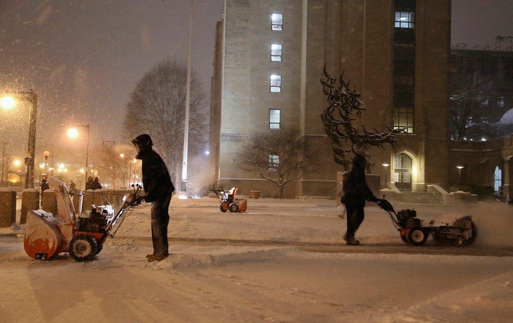 January 21, 2014 - Boston University Facilities and Management employees clear snow from Marsh Plaza after the start of winter storm Janus at 7:00pm on January 21, 2014. Photo by Taylor Hartz.
