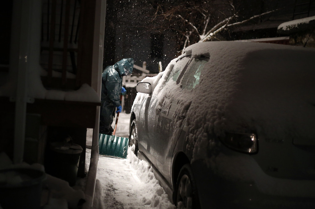 A man shovels his driveway on Pratt St. in Allston, Mass. on Jan. 21, 2014 as the winter storm Janus hits Boston.