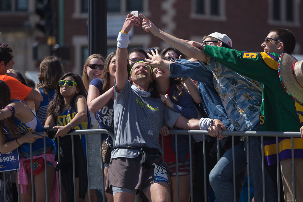April 21, 2014 – A runner stops to take a photo with spectators on Beacon Street in Boston, Mass., during the 118th Boston Marathon. Photo by Jun Tsuboike/BU News Service.