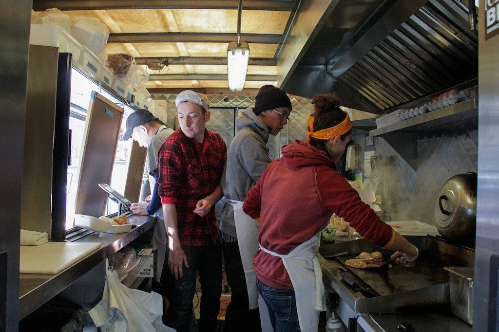February 7, 2014 - Caden Salvata, center, squeezes by his coworkers inside the Mei Mei food truck. The truck makes rounds dispensing asian-fusion food to various locations in Boston. Photo: Andrea Betenia/BU News Service.