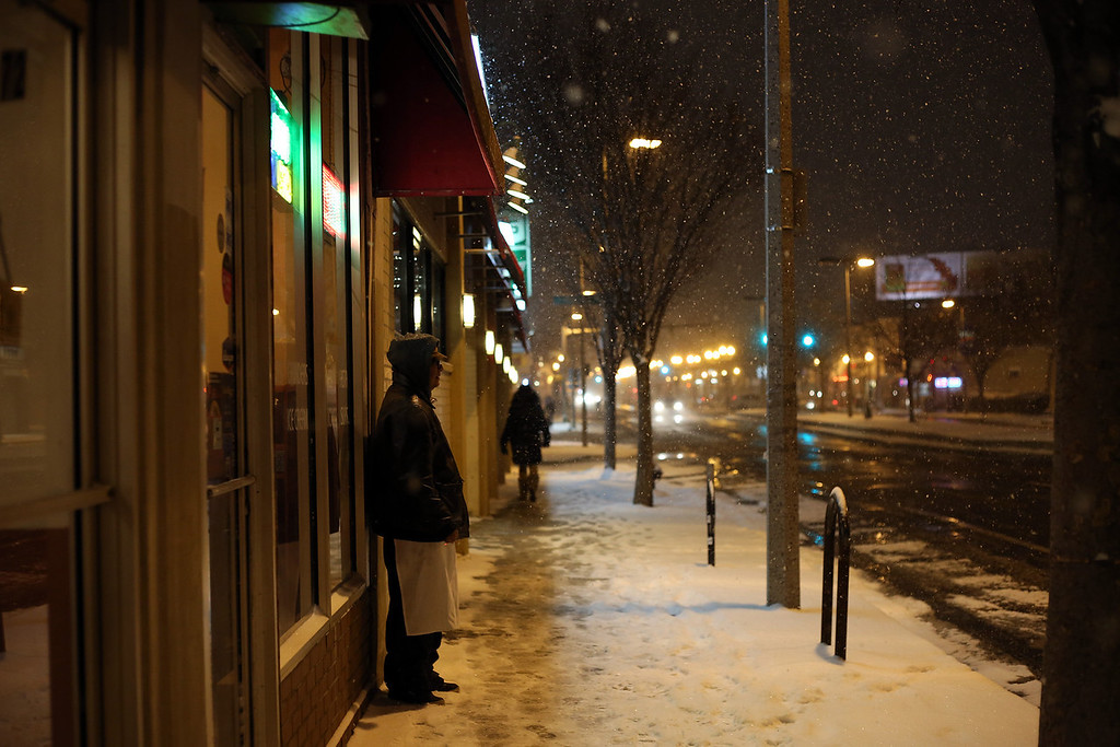A man takes a cigarette break in Allston, Mass. on Jan. 21, 2014 as the winter storm Janus hits Boston.
