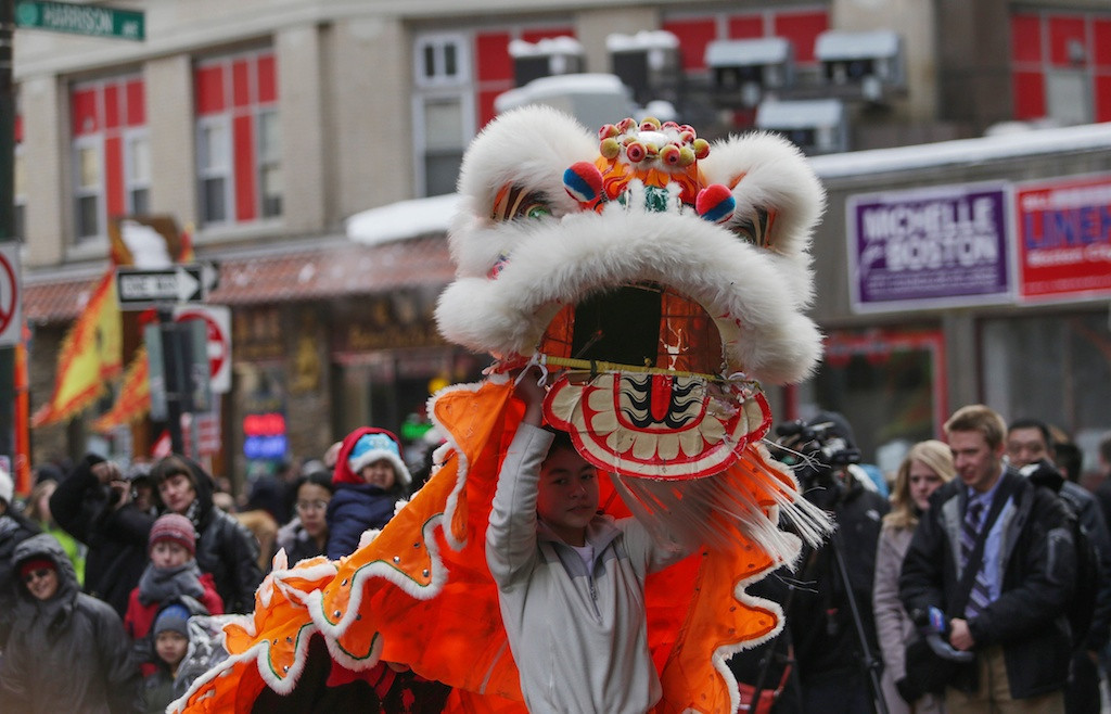 February 8, 2014 - A performer lifts up his costume in the middle of the lion dance, a Chinese tradition used to scare off evil spirits in the Chinese New Year Parade in Chinatown in Boston, Mass. Photo: Grace Donnelly/BU News Service.