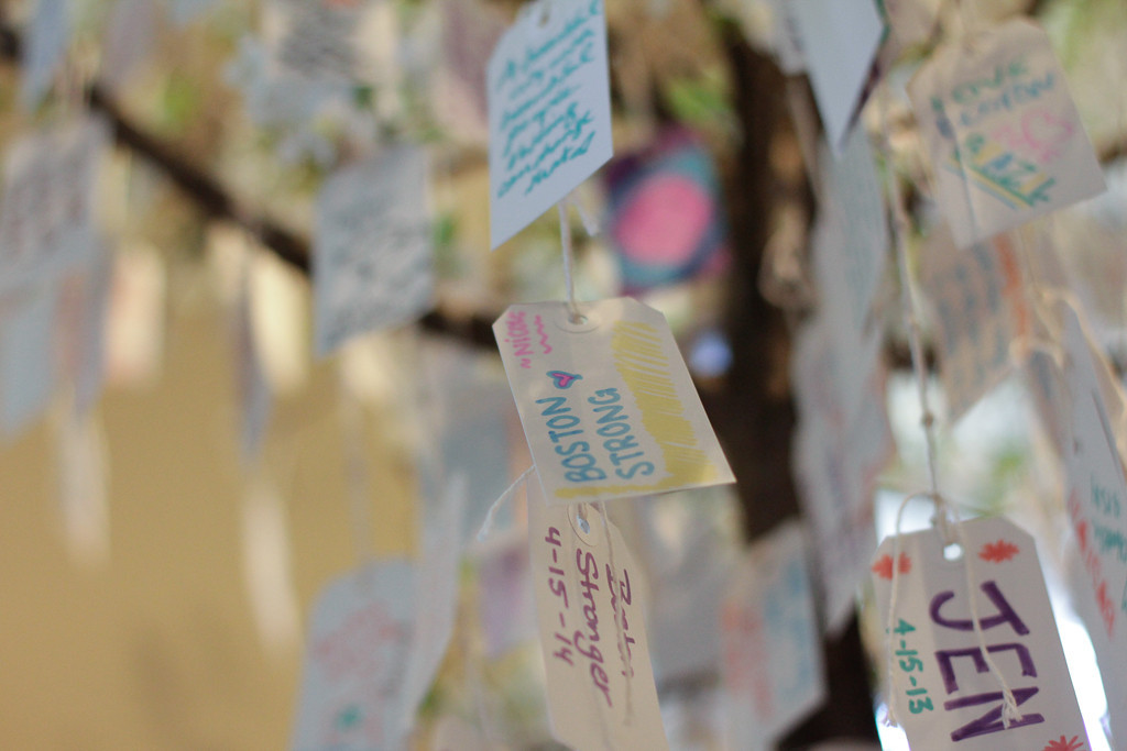 "April 16, 2014 - Hundreds of messages written on tags hang on trees inside of the Boston Public Library's ""Dear Boston"" exhibit. Photo by Andrea Betenia/BU News Service."