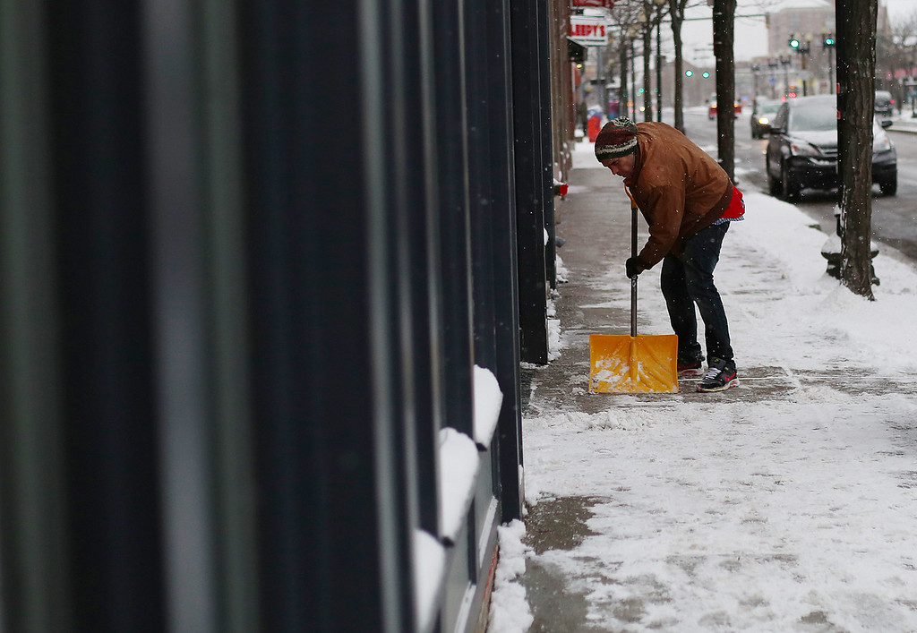 A man shovels the sidewalk on Brighton Ave. in Allston, Mass. on Jan. 22, 2014 as the winter storm Janus hits Boston. Photo by Grace Donnelly.