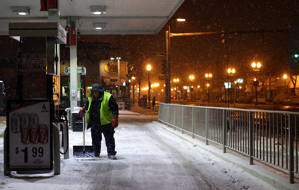 A man shovels at a gas station in Allston, Mass. on Jan. 21, 2014 as the winter storm Janus hits Boston.