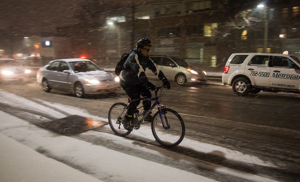 Boston, Jan. 21, 2014 -- A biker, center, slowly cycles along Commonwealth Avenue in Boston, MA, during the first few hours of Winter Storm Janus. Photograph by Carolyn Bick. ©BU News Service/Carolyn Bick 2014.
