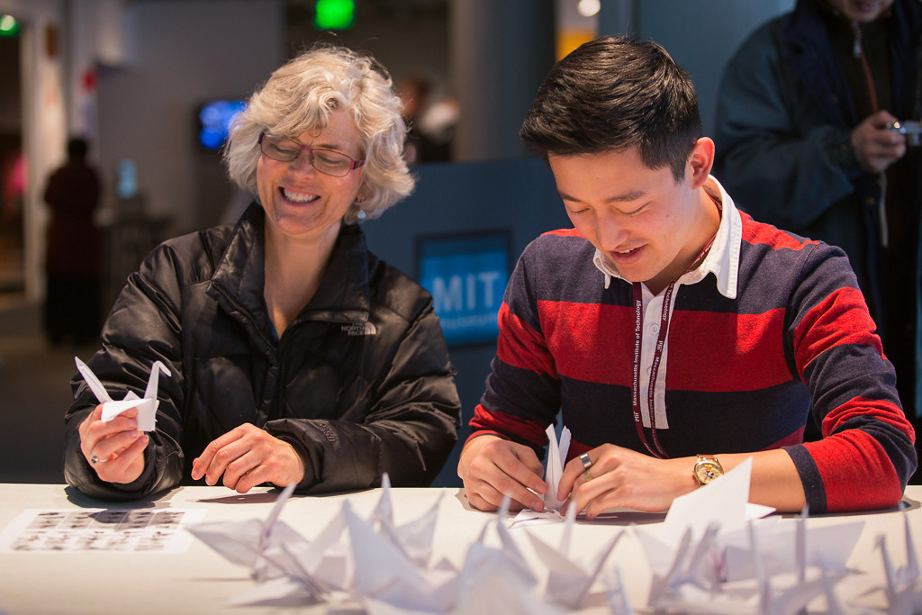 April 5, 2014 – Kathy Proctor, left, makes a paper crane after being instructed by the MIT Museum's public programs coordinator Andrew Hong, right, during a crane-folding event for Cranes for Collier, an installation project at the at the MIT Museum at 265 Massachusetts Ave., in Cambridge, Mass. The installation is dedicated to MIT Police Officer Sean Collier whokilled by the Boston Marathon bombings suspects in April 2013. Photo by Jun Tsuboike/BU News Service