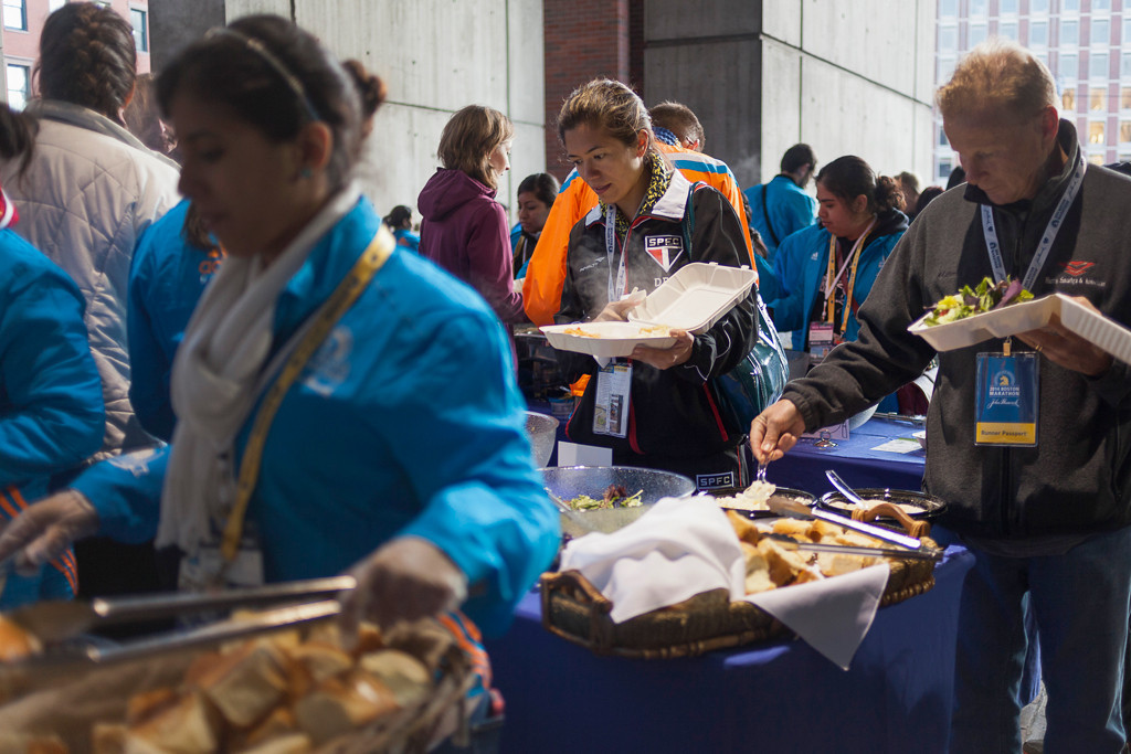April 20, 2014 - Runner Sharon Kusuke eats at the Boston Marathon Pre-Race Dinner, held at Boston City Hall Plaza. Photo by Dominique Riofrio/BU News Service.