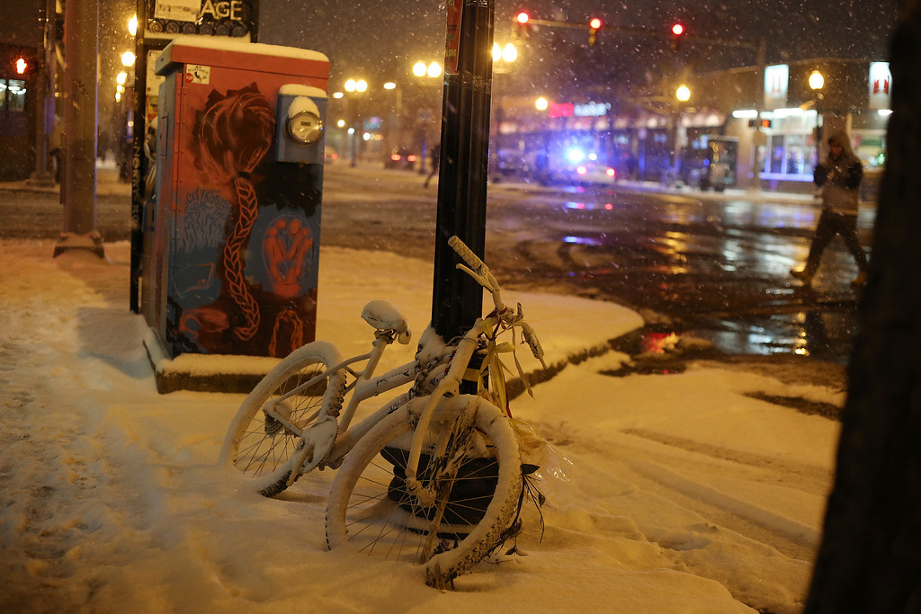 A bike sits covered in snow at the intersection between Brighton and Harvard Ave. in Allston, Mass. on Jan. 21, 2014 as the winter storm Janus hits Boston.