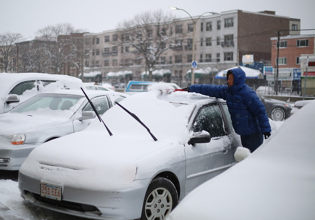 A man clears off his car on Commonwealth Ave. in Allston, Mass. on Jan. 22, 2014 as the winter storm Janus hits Boston. Photo by Grace Donnelly.