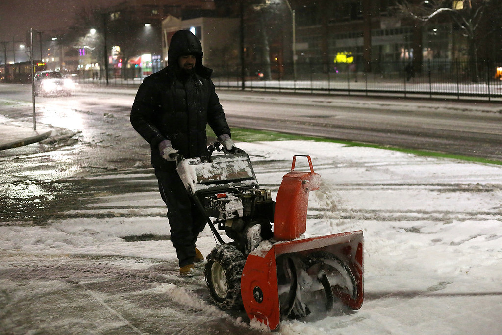 A man uses a snow blower outside of Shaws Supermarket in Allston, Mass. on Jan. 21, 2014 as the winter storm Janus hits Boston. Photo by Grace Donnelly.