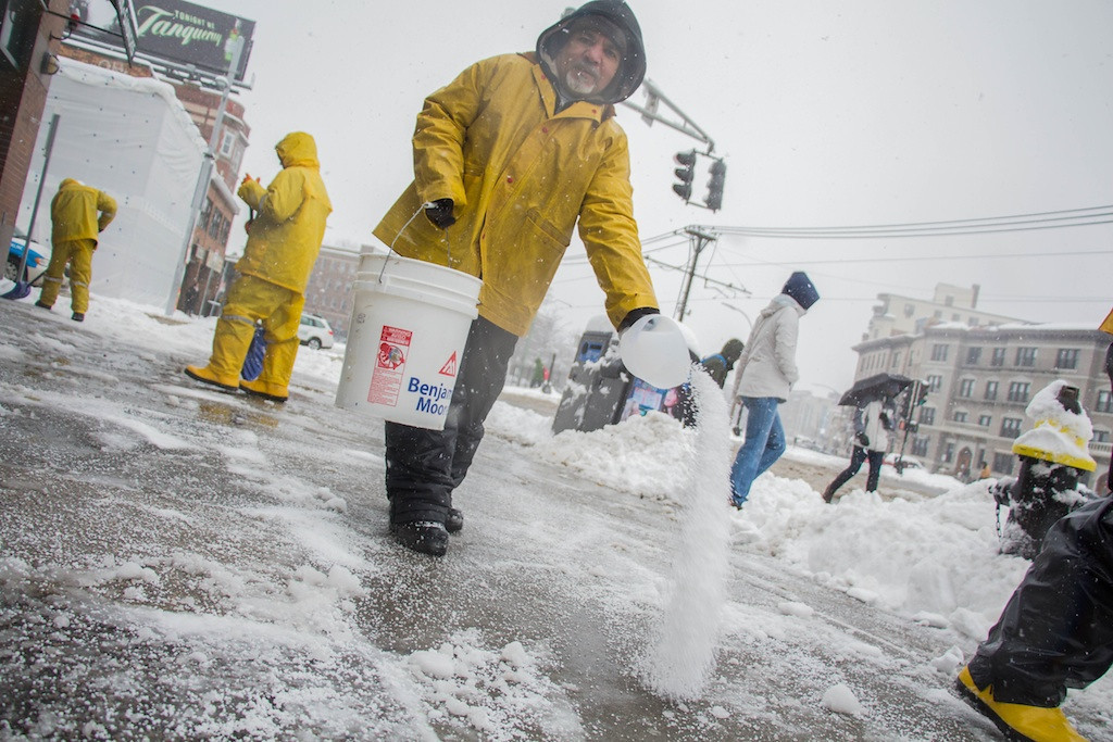 February 5, 2014 -  Valdir Dossontos, center, throws salt onto a Commonwealth Ave. sidewalk in Allston, Mass., while other workers around him shovel. Photo: Carolyn Bick/BU News Service.