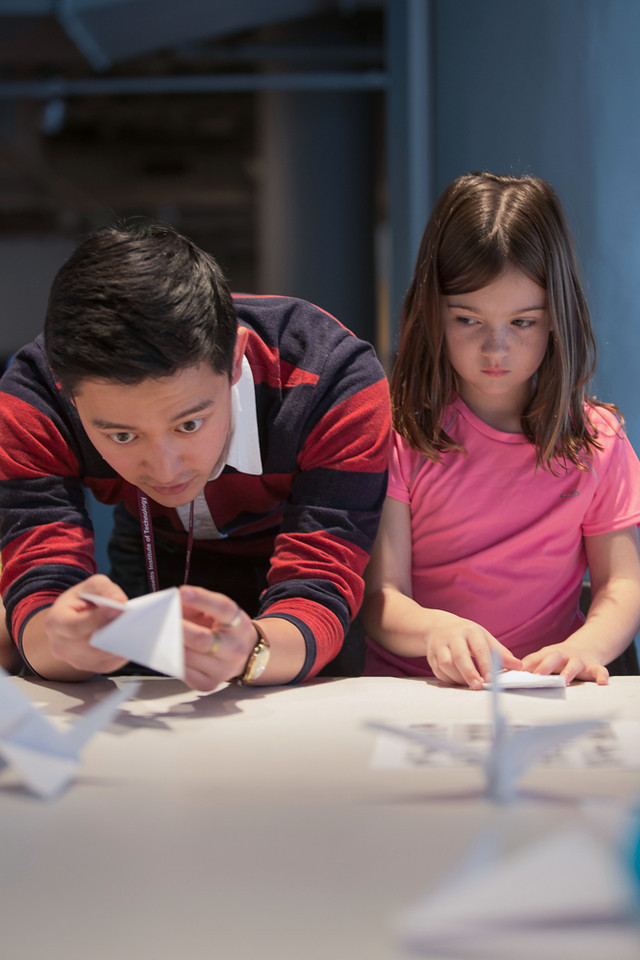 April 5, 2014 – The MIT museum's public programs coordinator Andrew Hong, left, teaches 7-year-old Shyah Mckinnon, right, how to fold a paper crane during a crane-folding event for Cranes for Collier, an installation project dedicated to MIT Police Officer Sean Collier who was killed by the two suspects responsible for the Boston Marathon bombings last year, at the MIT Museum at 265 Massachusetts Ave., in Cambridge, Mass. Photo by Jun Tsuboike/BU News Service