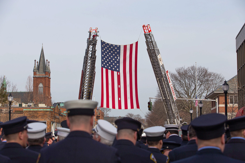 April 2, 2014 - Boston fire department ladders 14 and 17 raise a flag in memory of Lt. Edward Walsh Jr. as out-of-state firefighters line up to join his funeral procession in Watertown, Mass. Lt. Walsh was killed on duty while responding to a fire on Beacon St. in Boston, Mass., on March 26, 2014. Photo by Taylor Hartz/BU News Service.