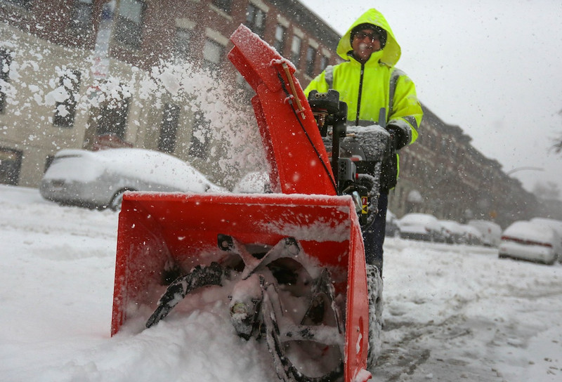 February 5, 2014 -Edourado José uses a snow blower to clear off sidewalks on Harvard Ave. and  Glenville Ave. in Allston, Mass. during a snow storm.  Photo: Grace Donnelly/BU News Service.