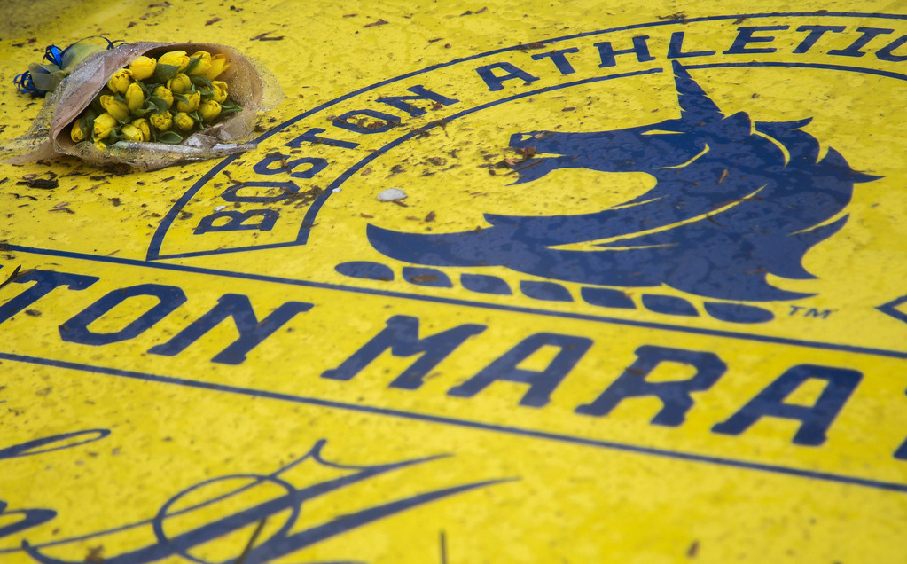 April 15, 2014 – A bouquet of flowers are placed on the finish line of the Boston Marathon on Boylston Street in Boston, Mass., for a tribute event for those affected by last year's bombings at the marathon. Photo by Jun Tsuboike/BU News Service