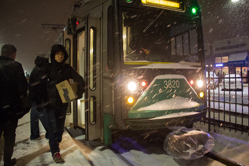 Allston, Jan. 21, 2014 -- Passengers exit B Line train at the Harvard Avenue station in Allston, MA, during the first few hours of Winter Storm Janus. An MBTA train driver, not pictured here, explained that the train's front protrusion, called a low bar, has been wrapped in plastic to protect it. Photograph by Carolyn Bick. ©BU News Service/Carolyn Bick 2014.