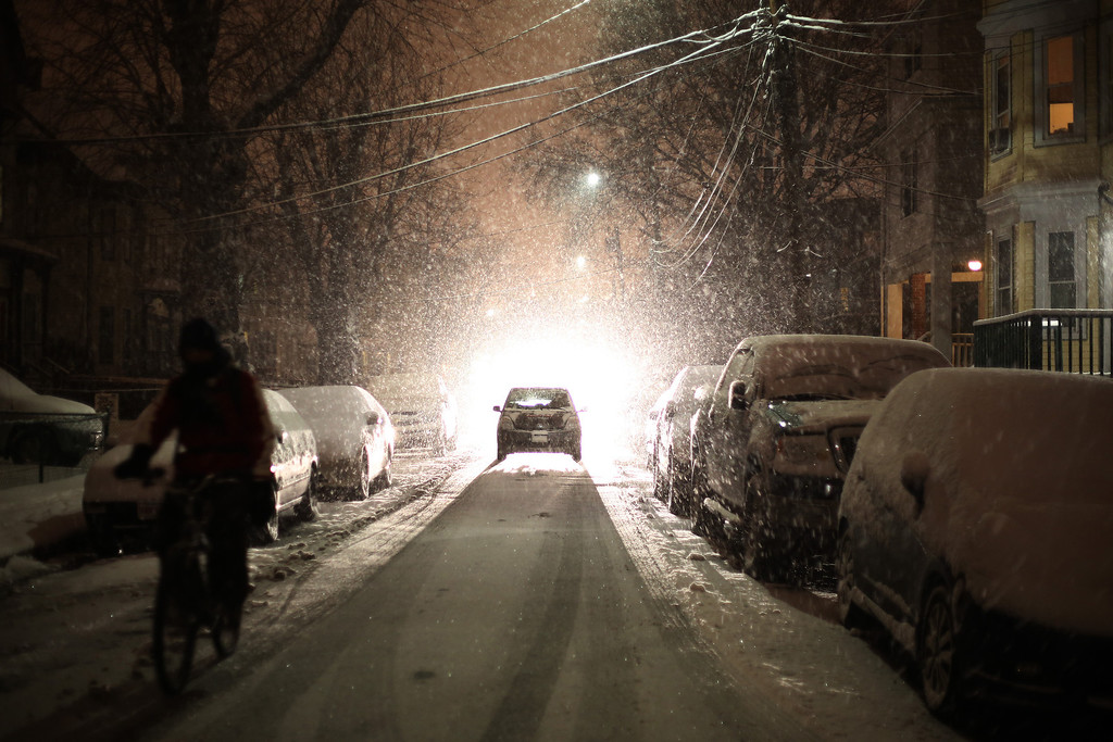 A biker and a car make their way down Farrington Ave. in Allston, Mass. on Jan. 21, 2014 as the winter storm Janus hits Boston.