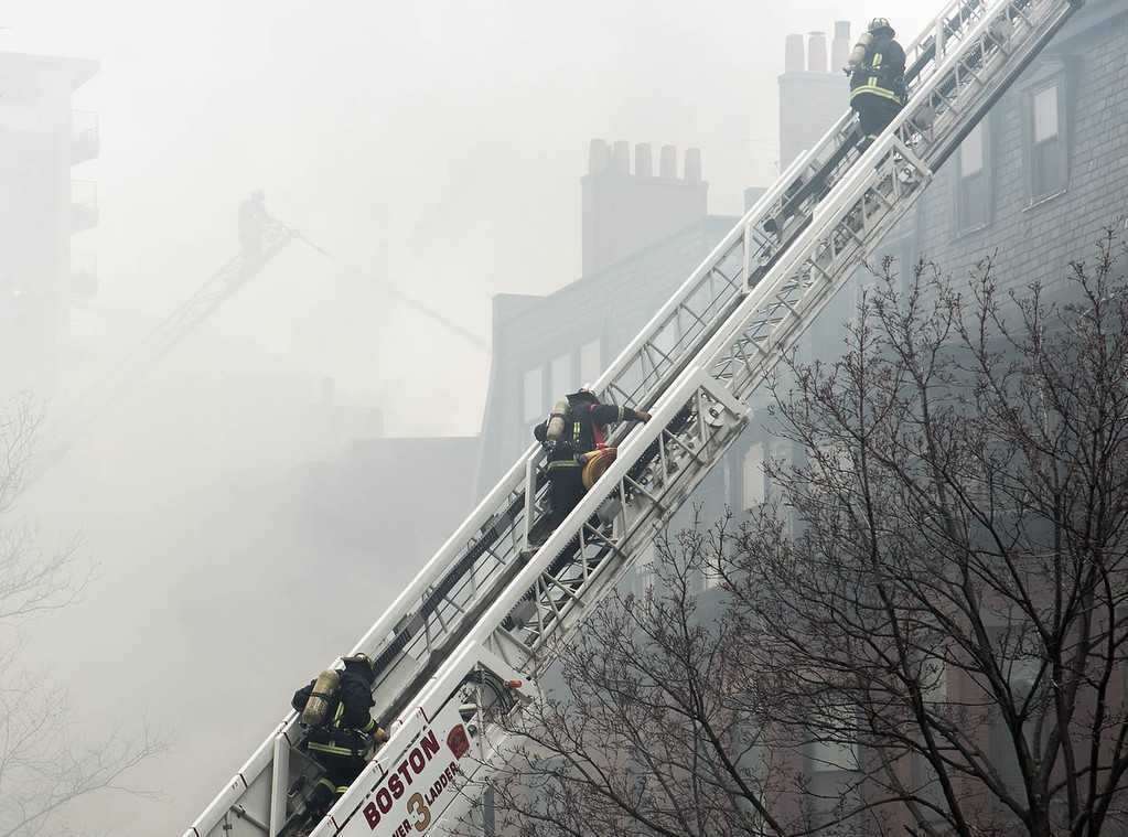March 26, 2014 - Firefighters climb a ladder while responding to a nine-alarm fire at 298 Beacon St. in Boston, Mass. Photo: Justin Saglio/BU News Service.