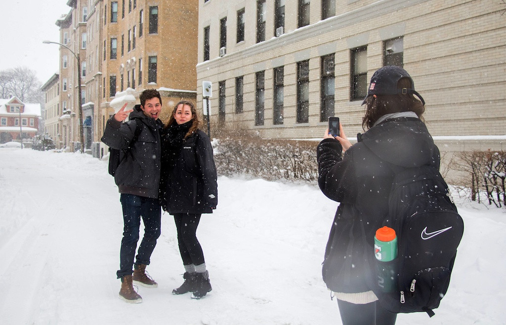 February 5, 2014 -   Boston University student Erin Pierce, right, takes photos of David Lacle, left, and Rachel Walden during a snow storm in Boston, Mass. Photo: Carolyn Bick/BU News Service.