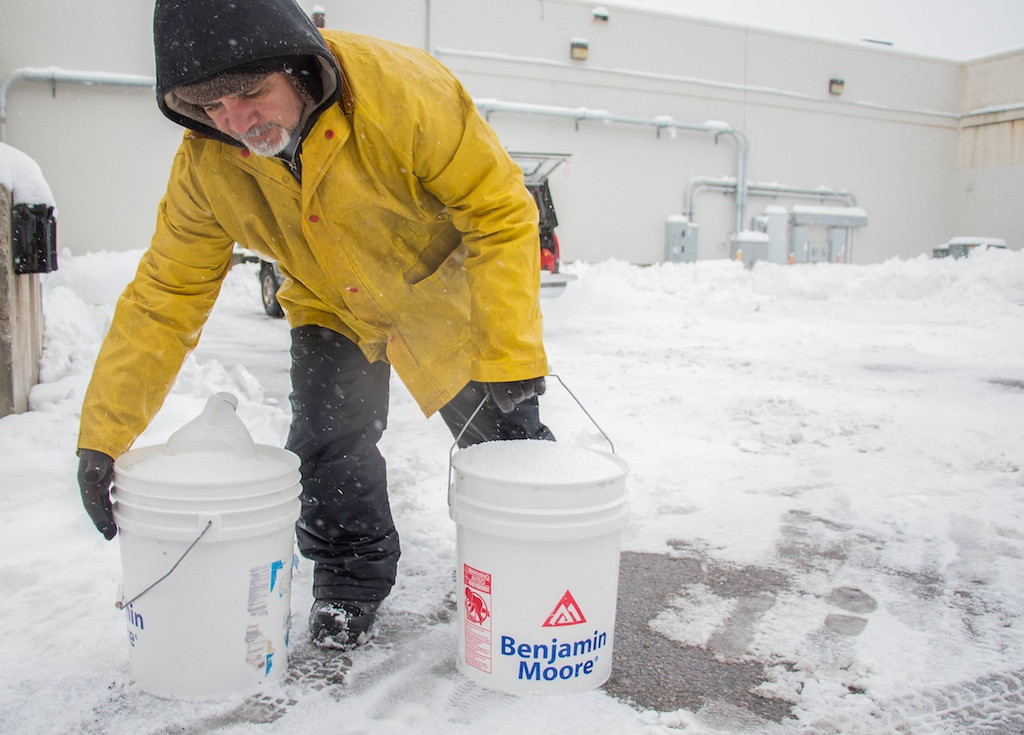 February 5, 2014 - Valdir Dossontos, picks up two buckets full of rock salt to use on a Commonwealth Ave. sidewalk in Allston, Mass. Photo: Carolyn Bick/BU News Service.