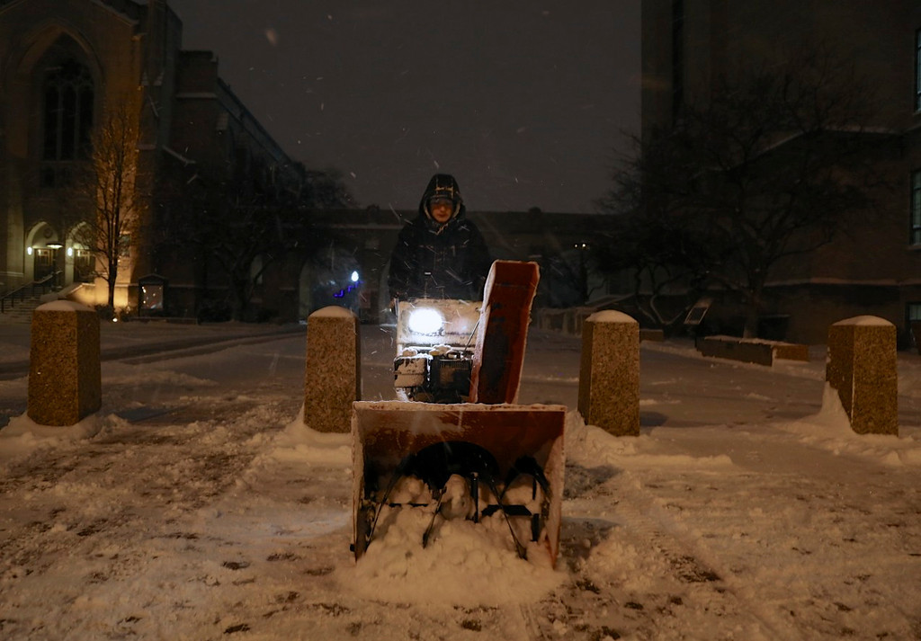 January 21, 2014 - A Boston University Facilities and Management employee clears snow from Marsh Plaza after the start of winter storm Janus at 7:00pm on January 21, 2014. Photo by Taylor Hartz.