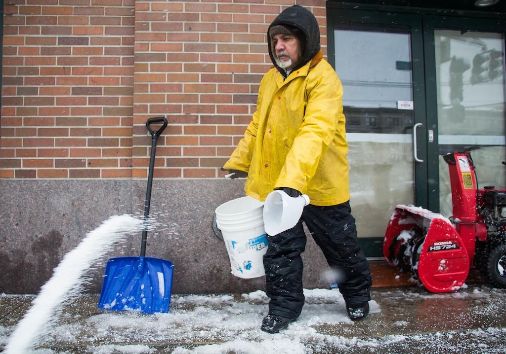 February 5, 2014 -  Valdir Dossontos throws salt onto a Commonwealth Ave. sidewalk in Allston, Mass. Photo: Carolyn Bick/BU News Service 2014.