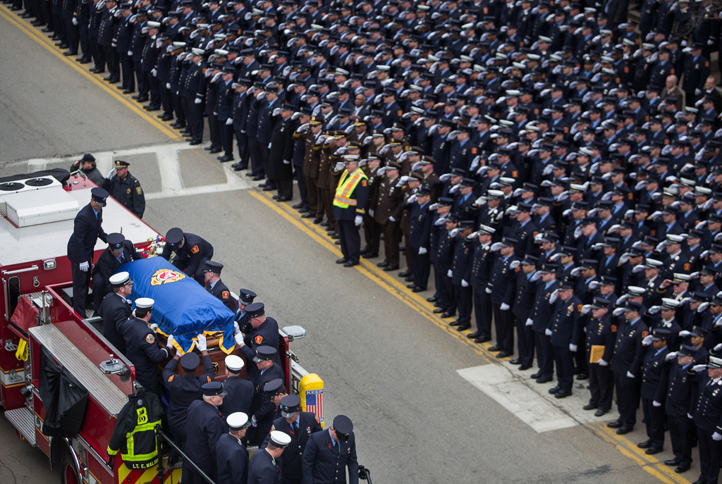 April 2, 2014 - Thousands of firefighters from across the nation line Main St. outside St. Patrick's church in Watertown, Mass., as the Boston Fire Department place the casket carrying Lt. Edward Walsh Jr. onto engine 33.Walsh, whose jacket and boots are placed on the left of the truck, responded to a Beacon St. fire in Boston, Mass., on engine 33 on March 26, 2014 and was killed on duty.  More than ten thousand firefighters attended the funeral. Photo by Taylor Hartz/BU News Service.