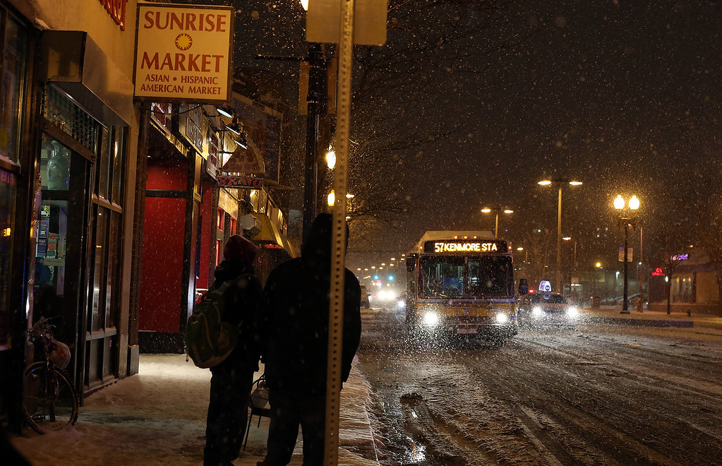Bostonians wait for the 57 bus in Allston, Mass. on Jan. 21, 2014 as the winter storm Janus hits Boston.