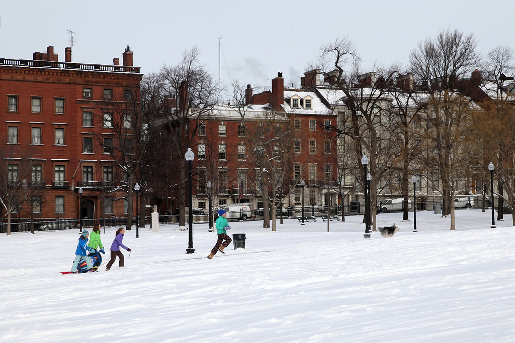 (From left) Annie Stockwell, Abbi Houghton, Camille Stockwell, and Bebe Stockwell chase their dog at the Boston Common in Boston, Mass., on Jan. 22, 2014.