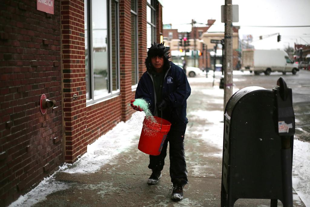 A man spreads salt on a sidewalk of Harvard Avenue in Allston, Mass. on Jan. 22, 2014 as the winter storm Janus hits Boston. Photo by Grace Donnelly.
