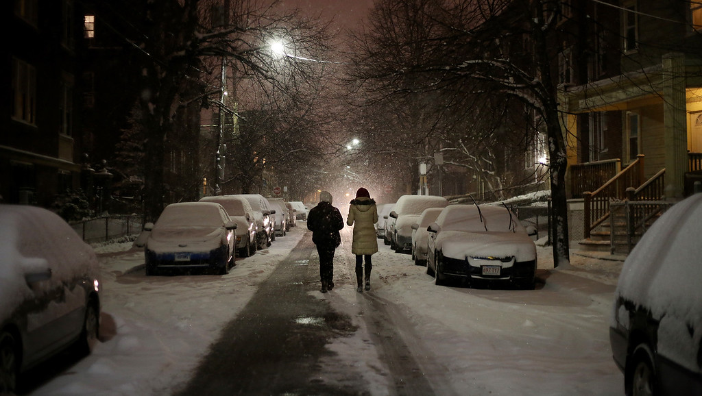 A couple makes their way down Chester St. in the middle of the road to avoid the snow on the sidewalks in Allston, Mass. on Jan. 21, 2014 as the winter storm Janus hits Boston.