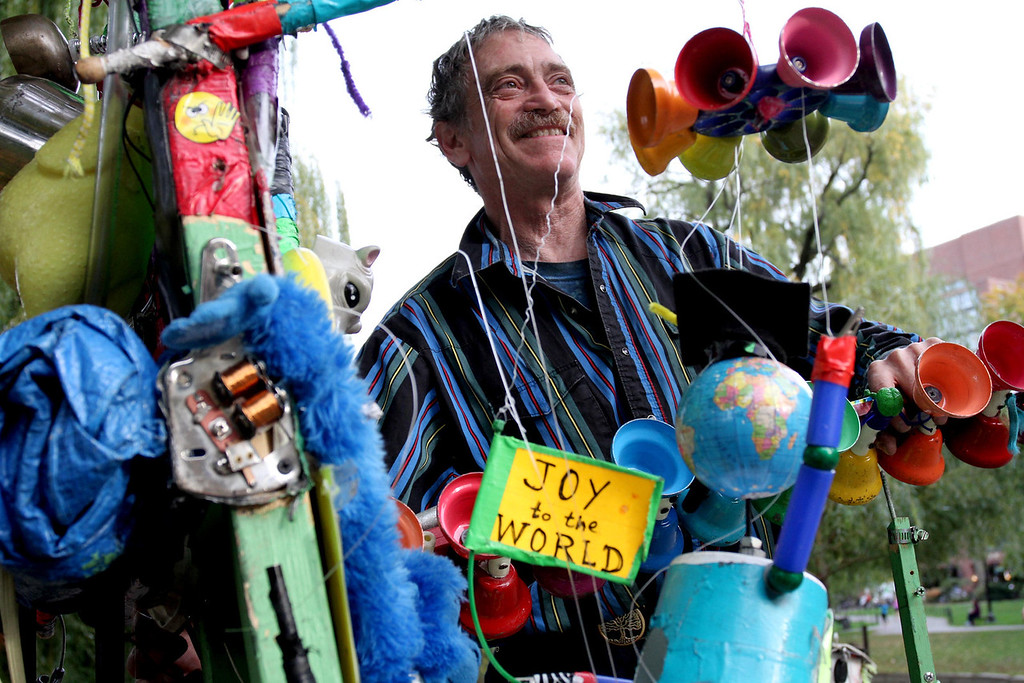 "Oct. 27, 2012 – Dan Friedman, who refers to himself as ""Ramblin' Dan The One Man Band,"" disassembles his ""Peace Wave Generator"" in the Public Garden in Boston, Massachusetts. According to Friedman, the elaborate instrument is comprised of items he has collected from his travels. ""This music machine takes the energy of music, turns it into peace waves, and broadcasts them to all the trouble spots of the world, thereby attempting to achieve world peace through street music."" Photo by Billie Weiss."