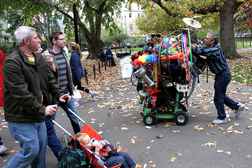 "Oct. 27, 2012 – Dan Friedman, who refers to himself as ""Ramblin' Dan The One Man Band,"" pushes his fifty pounds of gear after performing in the Public Garden in Boston, Massachusetts. Friedman was studying botanical sciences as a graduate student at the University of Texas, Austin before dropping out and deciding to become a full-time street performer. ""I picked up some street musicians hitch hiking and started jamming with them between classes. I just never came back because we were having too much fun."" Photo by Billie Weiss."