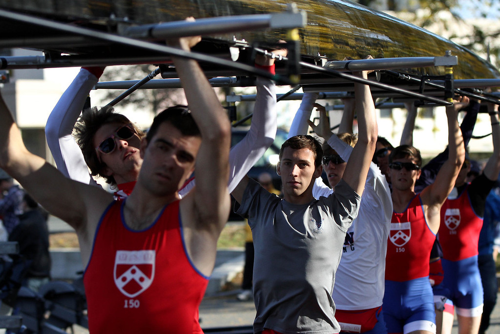 Oct. 21, 2012 – (Left to center) Juniors T.J. Smith and Sam Shaw, Senior James Shovelin, and other members of the University of Pennsylvania men's lightweight rowing team carry their racing shell to the launching docks before racing in the 2012 Head Of The Charles Regatta in Boston, Massachusetts. Photo by Billie Weiss.