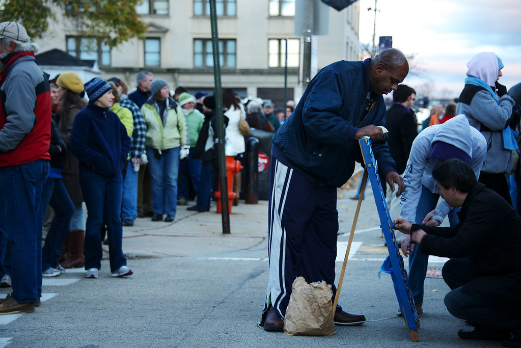 Nov. 4, 2012 – Truck driver, Tom Jackson, sells buttons supporting President Obama early Sunday morning at Capitol Square in Concord, N.H. to supporters waiting in line for President Obama's grassroots rally to begin. President Obama and former President Clinton teamed up to rally voters in New Hampshire who could make the difference in this year's presidential race. Photo by Cat Ring.