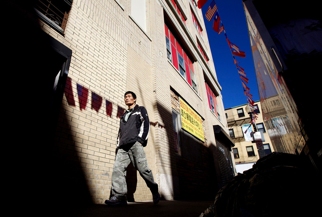 A man walks down Tyler Street, in Boston's Chinatown, during a sunny morning on October 11, 2012. (Photo by Michael Cummo)