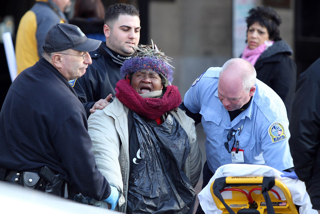 A homeless woman gets taken away on a stretcher in front of Park Street Station on January 30, 2012 at the Boston Common, Boston, Mass.