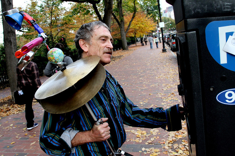 """Oct. 27, 2012 – Dan Friedman, who refers to himself as """"Ramblin' Dan The One Man Band,"""" feeds a parking meter outside the Public Garden in Boston, Massachusetts. """"I come in early every day to get my parking spot so I don't get a ticket. I've been here since nine o'clock this morning,"""" he said. Friedman has lived in a co-op in Cambridge, Massachusetts for the past four years, and makes his living performing on Boston Common and in Harvard Square. Photo by Billie Weiss."""