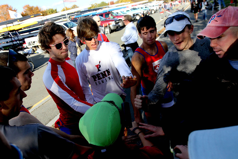 """Oct. 21, 2012 – Members of the University of Pennsylvania men's lightweight rowing team huddle around head coach Nick Baker (far right, red hat) before racing at the 2012 Head Of The Charles Regatta in Boston, Massachusetts. """"You shouldn't need any extra motivation today. This is the Head Of The Charles,"""" said Baker. Photo by Billie Weiss."""