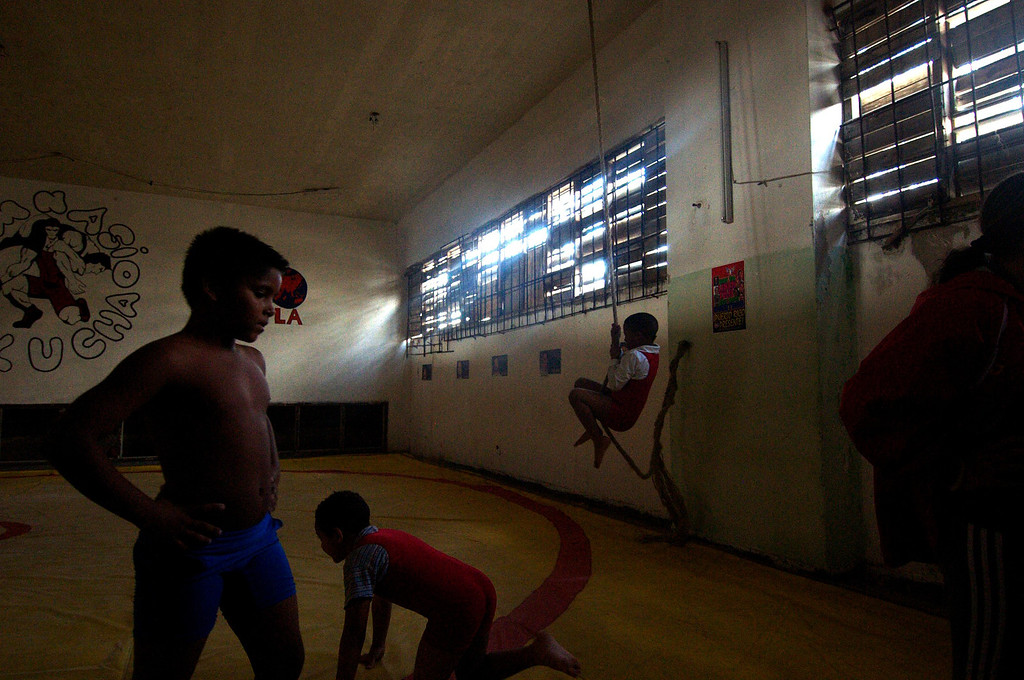 Children play before their wrestling lesson inside the Parque Jose Marti Stadium in Havana, Cuba on March 26, 2013. Their parents sit and watch the entire lesson while the kids learn how to wrestle, jump, stretch, and most importantly have fun. (Photo by: Michael Cummo)