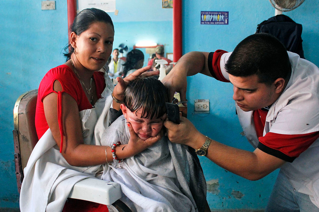 A young boy squirms in his mother's lap while getting his hair cut in Cardenas, Cuba on March 30, 2013. Photo by Stacey Rupolo/BU News Service.