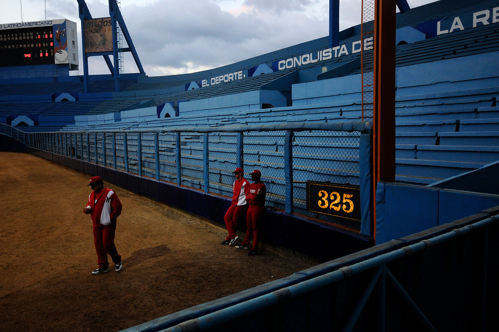 Members of the Matanzas watch their teammates warm up before a rivalry game against the Industriales Blue Lions at the Estadio Latinamerico in Havana, Cuba on March 28, 2013. (Photo by: Michael Cummo)