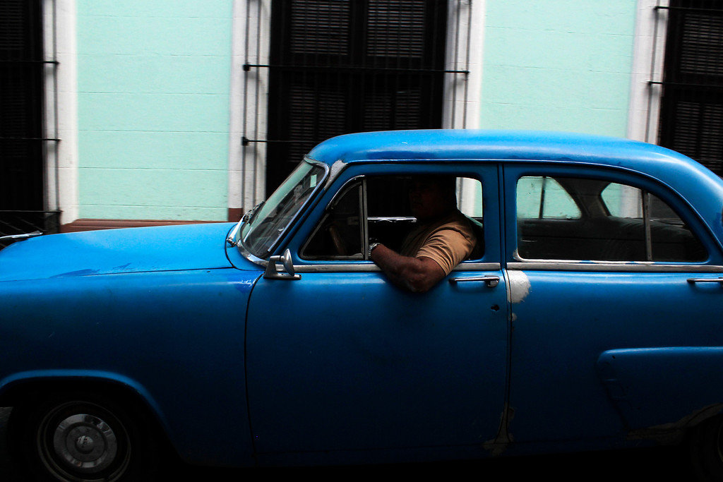 A man leans out the window of his car while driving in Havana, Cuba on March 29, 2013. Photo by Stacey Rupolo/ BU News Service.