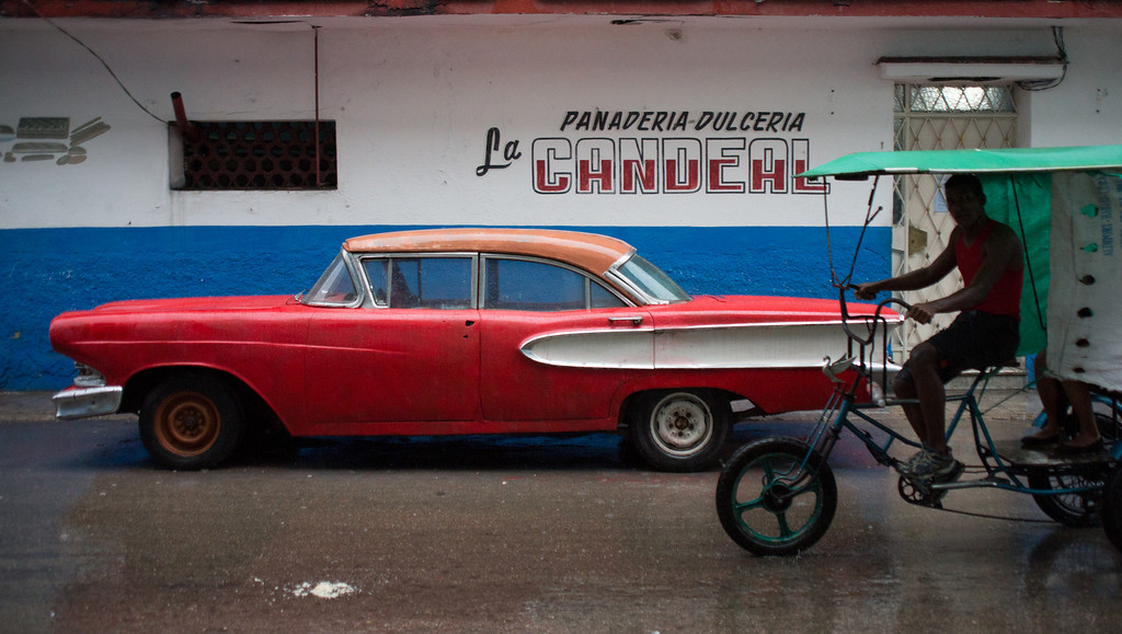 A bike taxi pedals by a parked car in Havana. Due to the trade embargo with the United States, many Cubans drive vehicles manufactured before the 1959 revolution. Photo by Sarah Ganzhorn / BU News Service