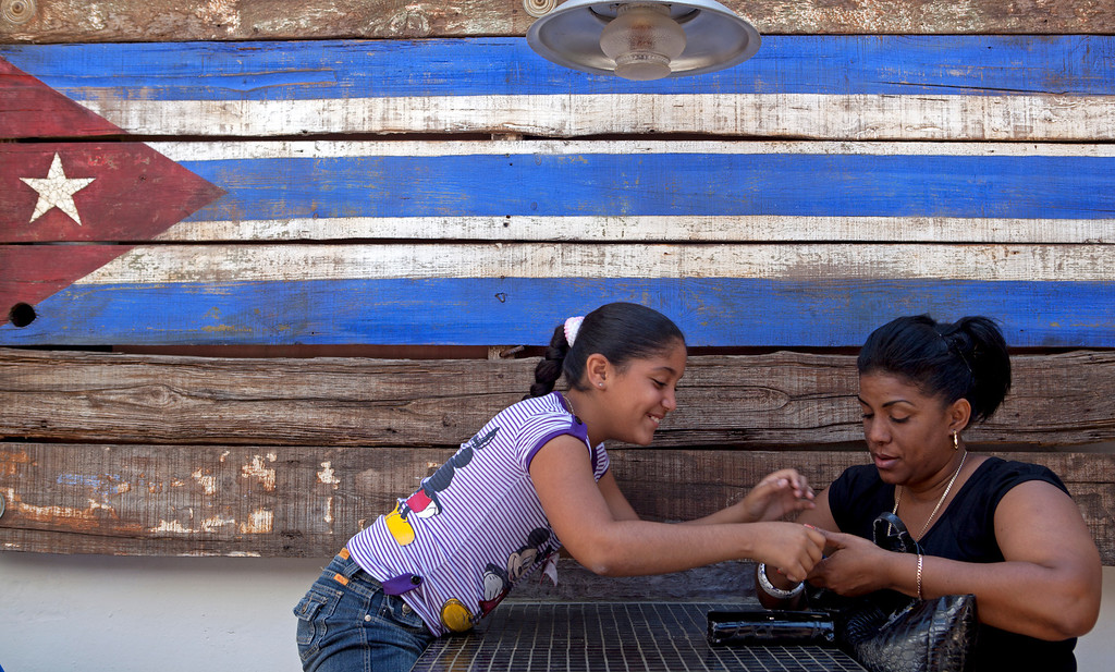 March 29, 2013- A girl and her mother react to a cellphone message in a restaurant in Cardenas, Cuba on Friday. Photo by Melanie Rieders.