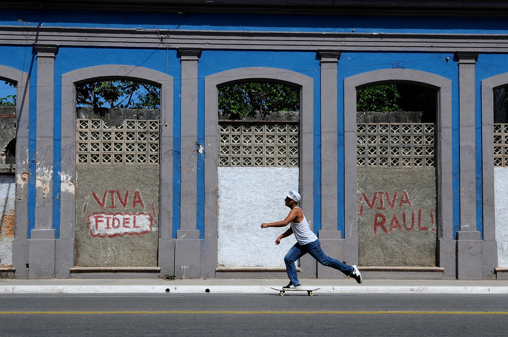 A teen skates by grafitti in the city of Cardenas, Cuba on March 30, 2013. The younger generations of Cubans are frustrated by the current regime and situation, but have no power or collective voice. (Photo by: Michael Cummo)