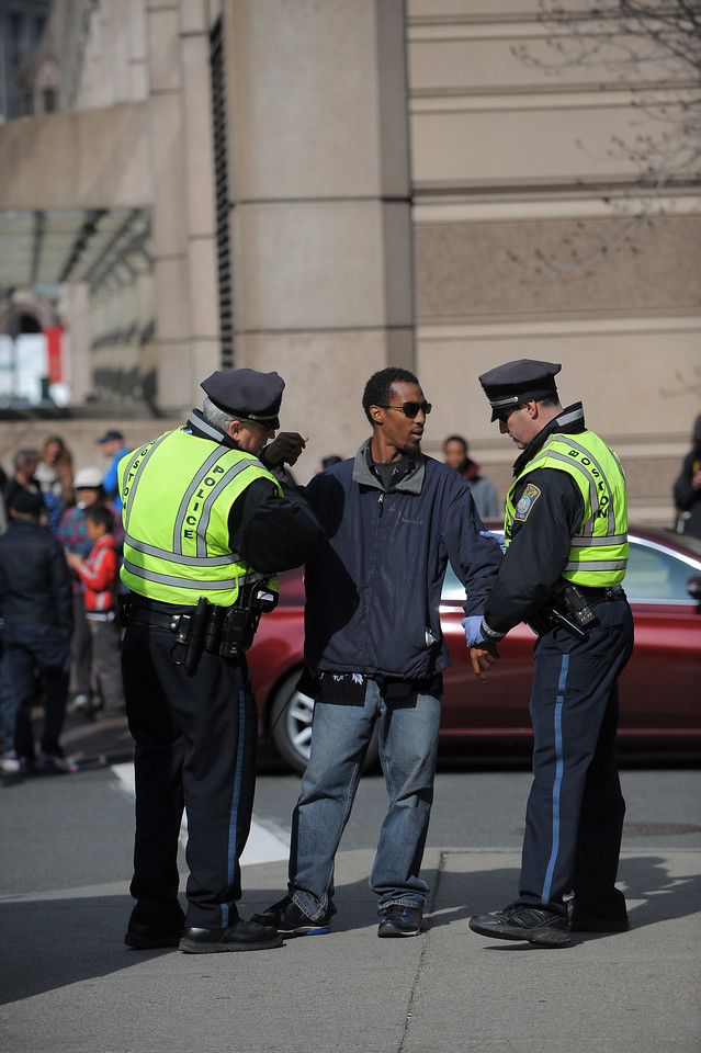 Boston, MA, April 15, 2013: Two explosions went off in Copley Square, directly after the finish line of the Boston Marathon. Boston police frisk a random passerby. Photo by: Michael Cummo