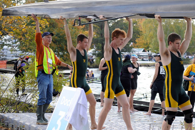 """Oct. 20, 2012 - Peter Dirks, a volunteer for the Head of the Charles Regatta, lifts the stern of the boat for the College of William and Mary rowing club before they participate in the race on Saturday in Boston, Mass. Out of nine total docks along the Charles River, Dirks helped bring in and launch boats from Dock Three. """"This is a very controlled dock,"""" Dirks said. """"If you want to see mayhem, go to Dock Seven or Eight."""" Photo by Rachel Schowalter."""
