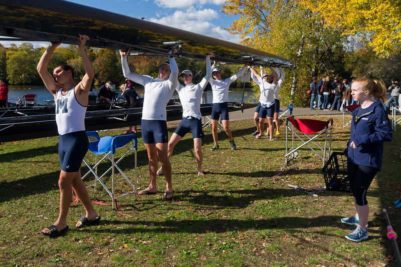 """October 21, 2012 - Freshman coxswain Caroline Moynihan, right, directs the Middlebury varsity men's eight team as they move their sweep boat to the water prior to racing in the Head of the Charles Regatta, the world's largest 2-day rowing event. Moynihan, who had only been coxing for three weeks prior to the race, said, """"The hardest thing will be focusing on both the steering and motivation. I might not say as much to them because I'll be focusing but hopefully I can balance it out."""" Photo/Christopher Weigl"""